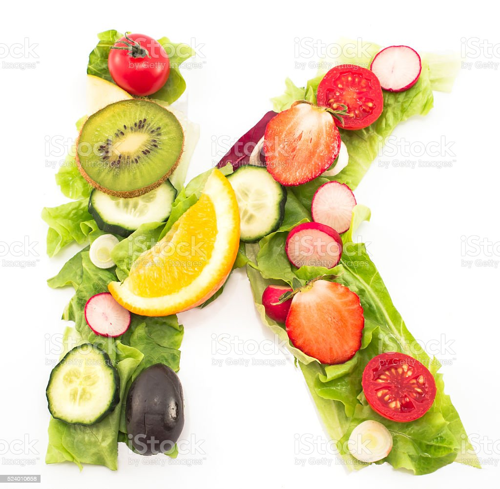 Letter K made of salad and fruits stock photo