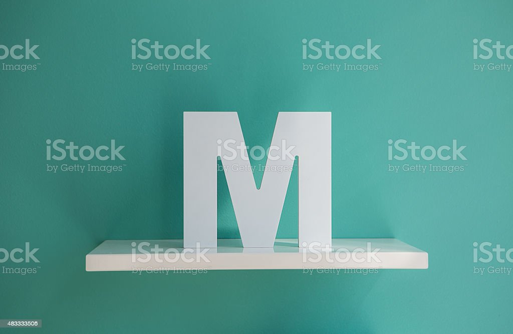 Letter M turquoise color on a white shelf stock photo