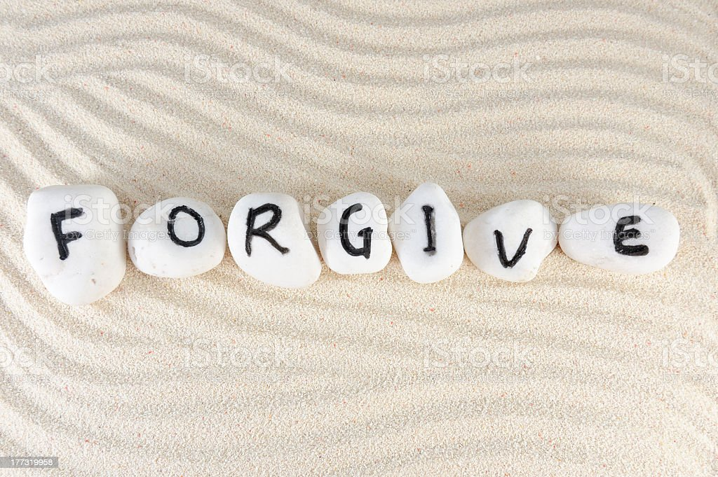 Letter painted rocks arranged to form the word 'forgive' stock photo