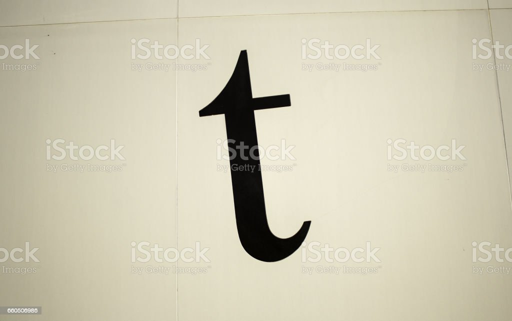 Letter t on the wall stock photo