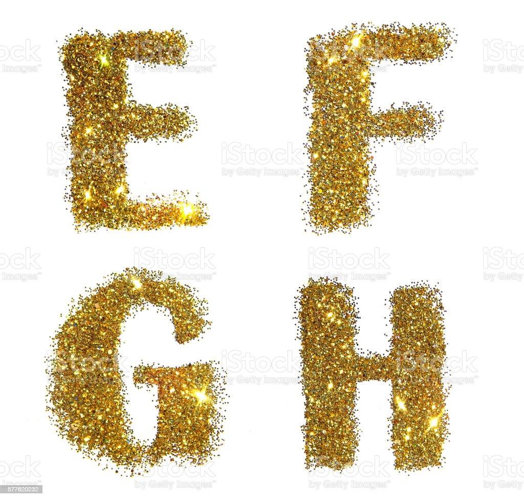 Letters E, F, G, H of golden glitter on white stock photo