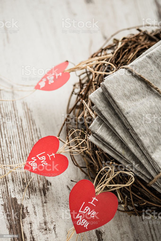 Letters in a nest and hanging hearts stock photo