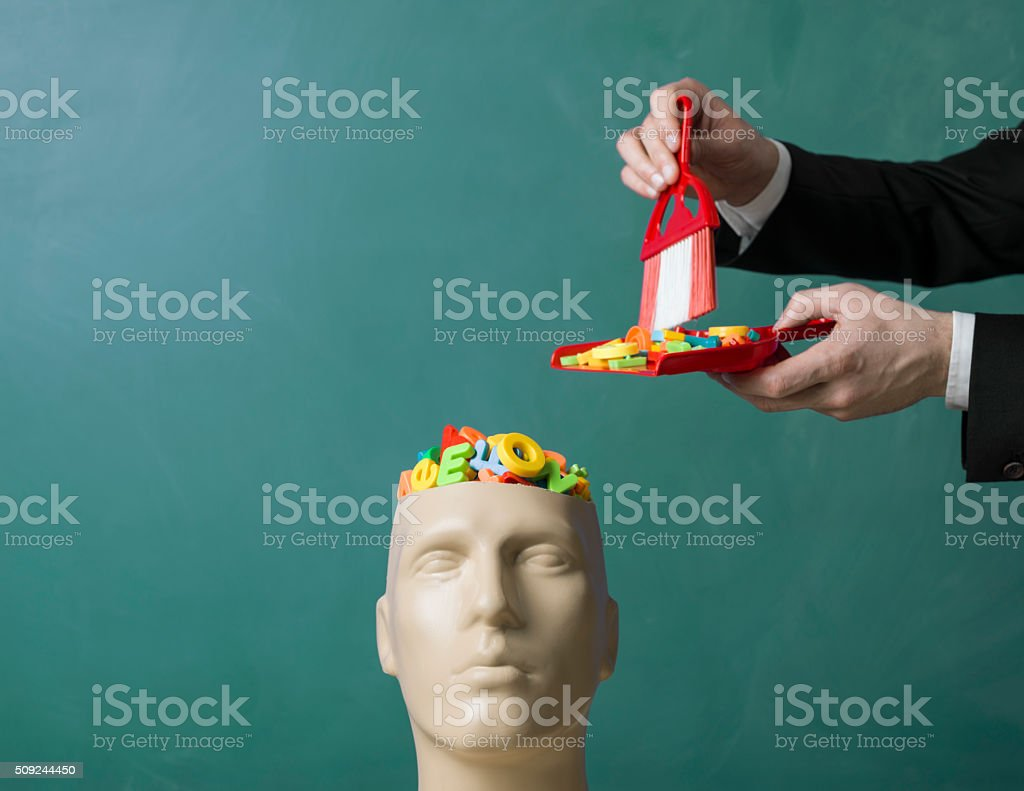 Letters in plastic mannequin head over blackboard for information pollution stock photo