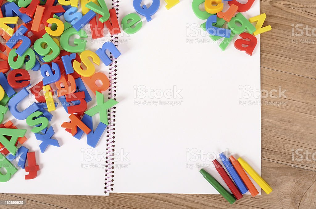 Letters of alphabet with notebook on school desk royalty-free stock photo