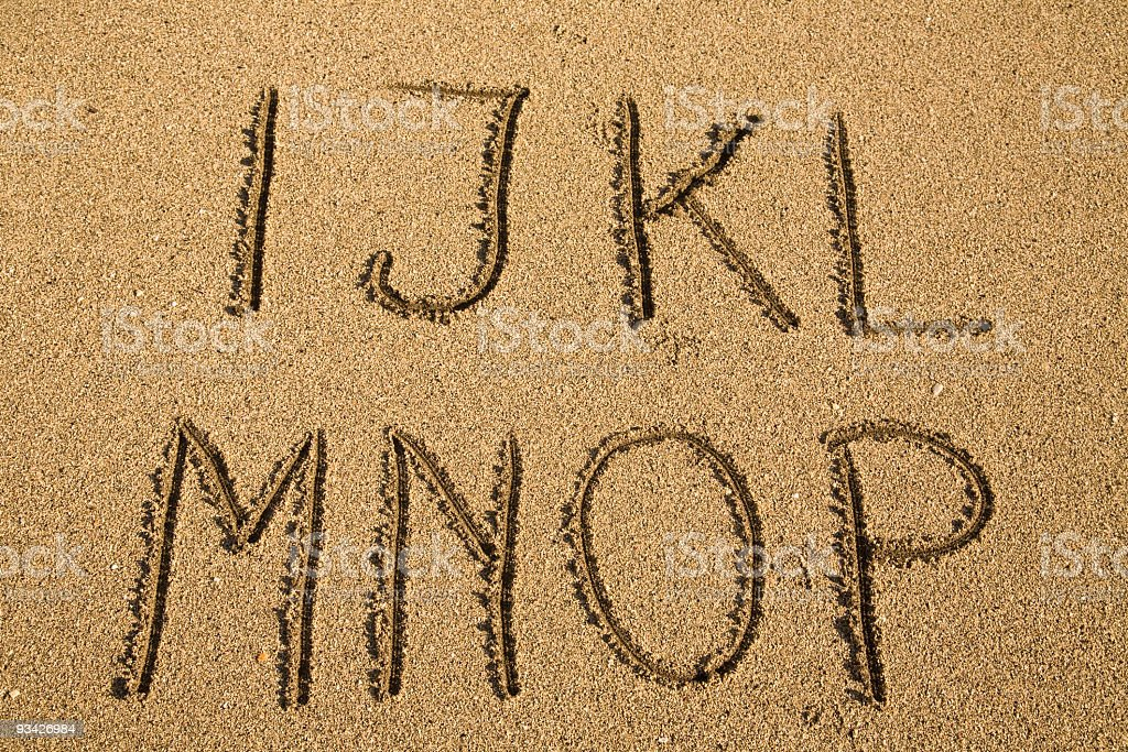 Letters of the alphabet drawn into the sand royalty-free stock photo