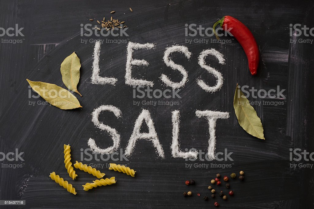 LESS SALT letters, spices and herbs on a blackboard stock photo