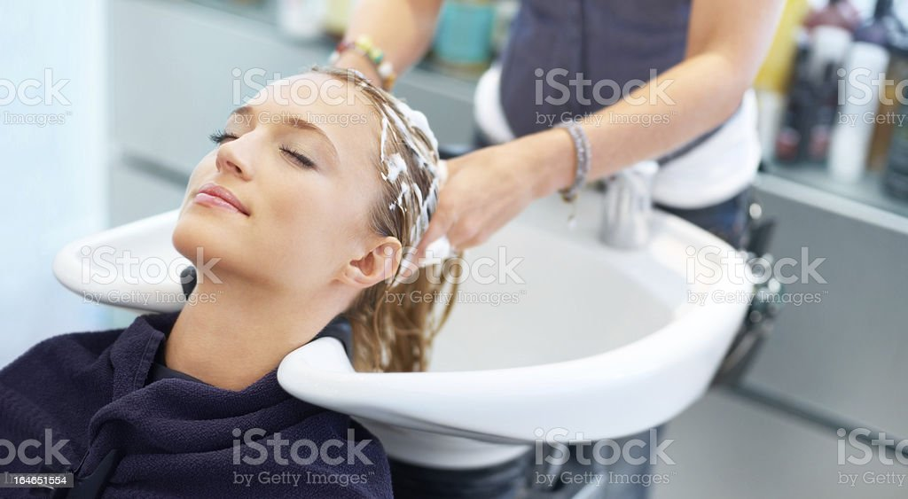 Letting experienced hands treat her tresses royalty-free stock photo