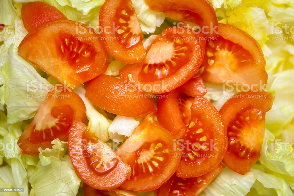 Lettuce leaves and tomato pieces on a plate, salad background. stock photo
