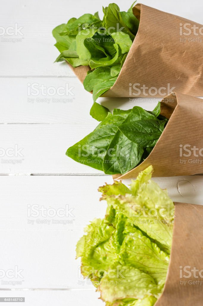 Lettuce, spinach, rucola packed in a paper bag on a white wooden table stock photo