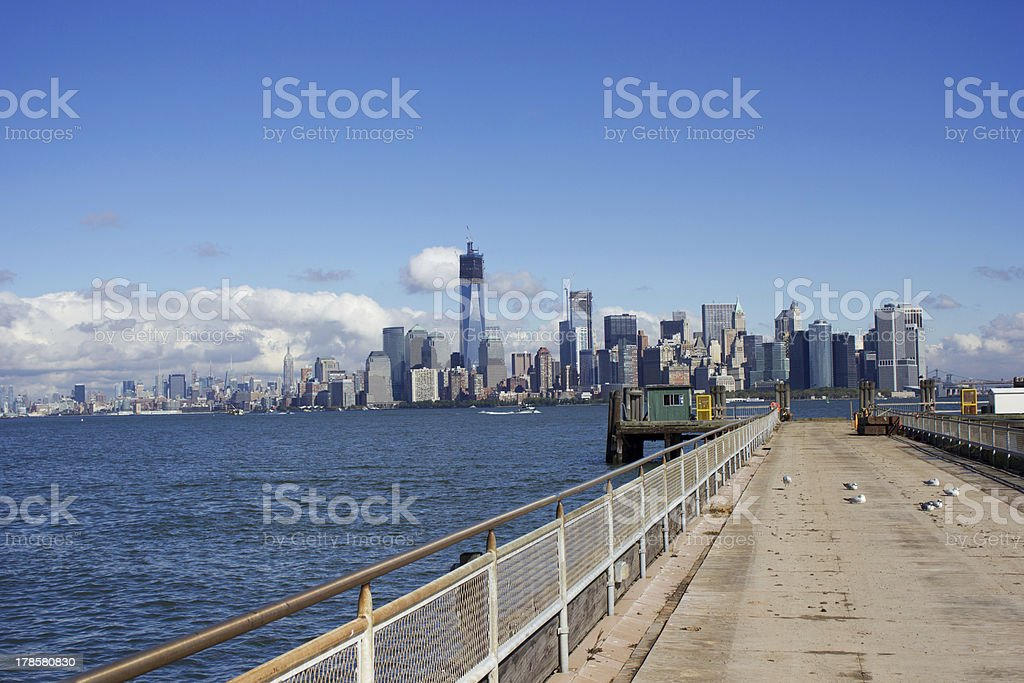 Liberty Island pier in front of Manhattan royalty-free stock photo