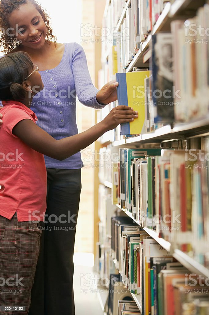 Librarian and young girl choosing a book stock photo