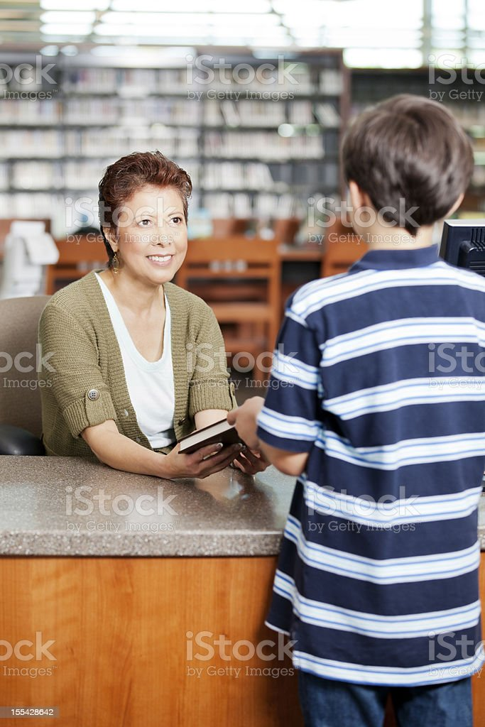 Librarian handing a book to little boy at checkout stock photo