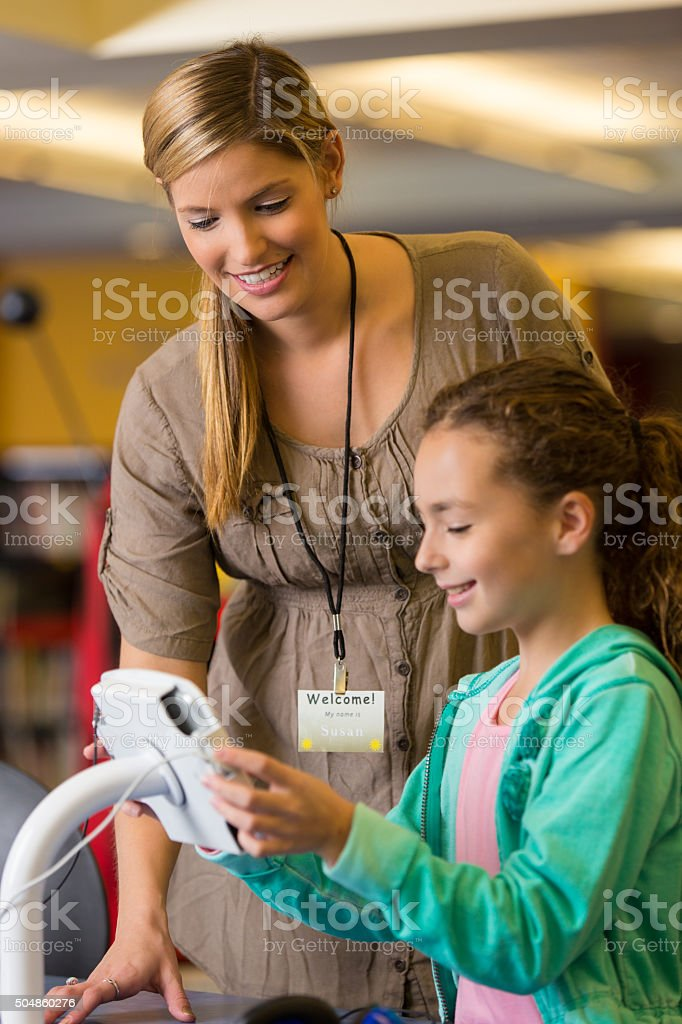Librarian helping elementary age girl with digital tablet in library stock photo