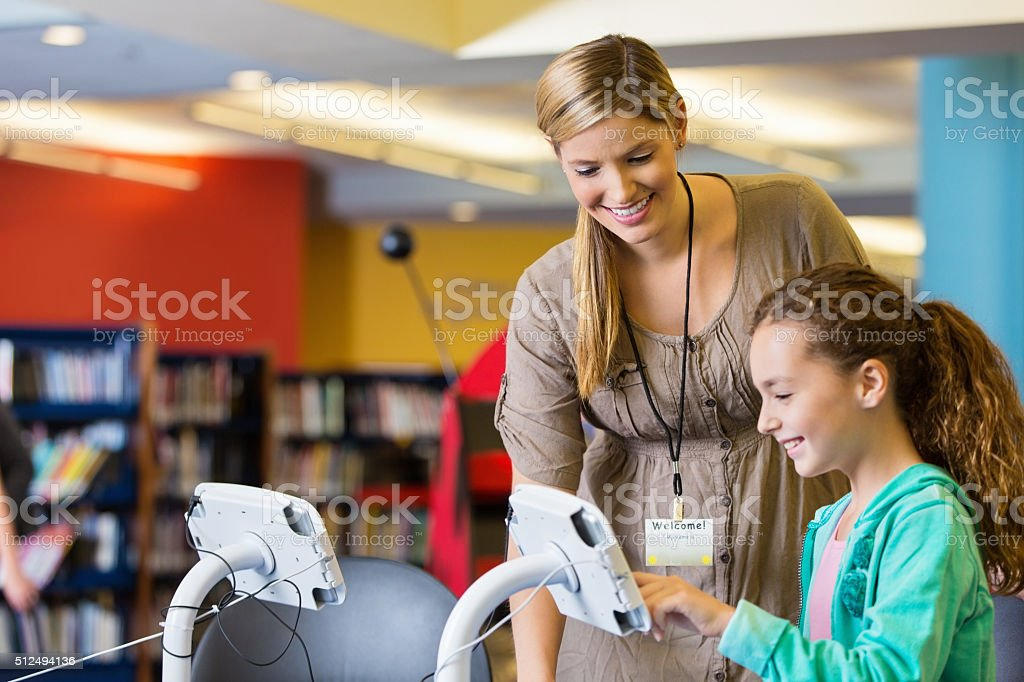 Librarian helping elementary age girl with digital tablet technology stock photo