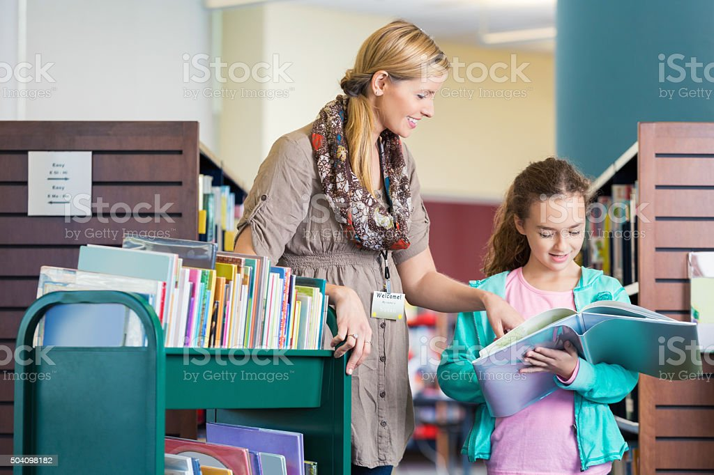 Librarian helping elementary age student read book in library stock photo