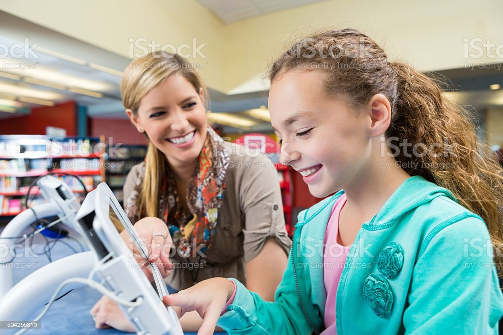Librarian helping elementary student use digital tablet in library stock photo