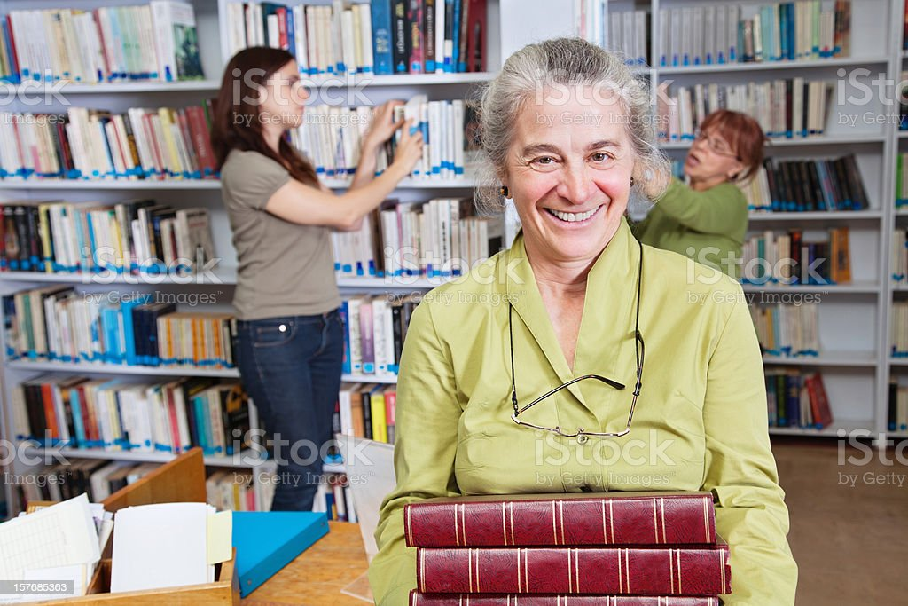 Librarian Holding Stack of Books in Library royalty-free stock photo