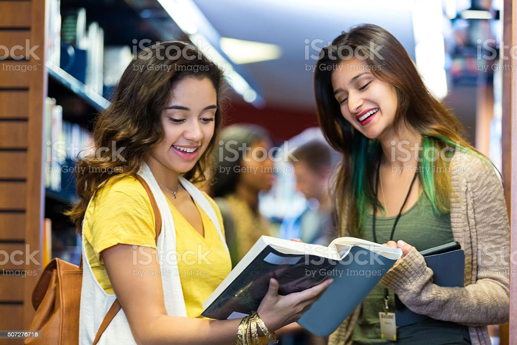 Librarian or library aid helping college student with book stock photo