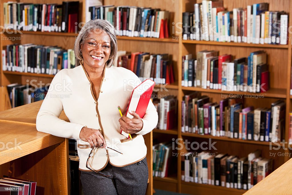 Librarian or teacher in library stock photo