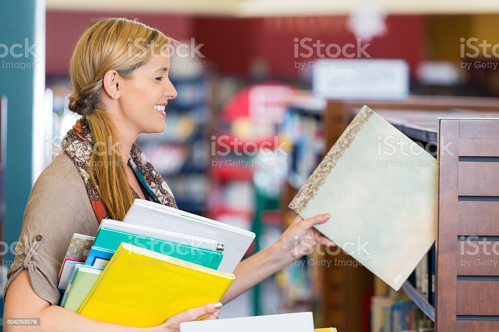 Librarian putting books away in children's section of public library stock photo