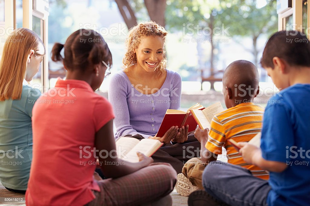 Librarian reading to a group of children stock photo