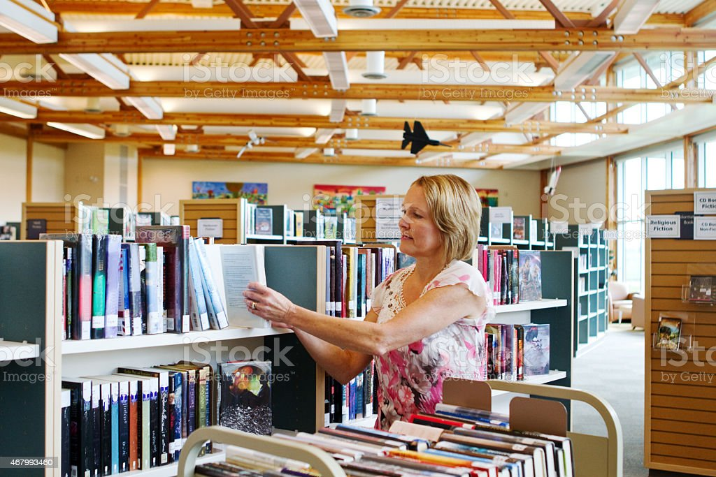 Librarian replacing books on shelves stock photo