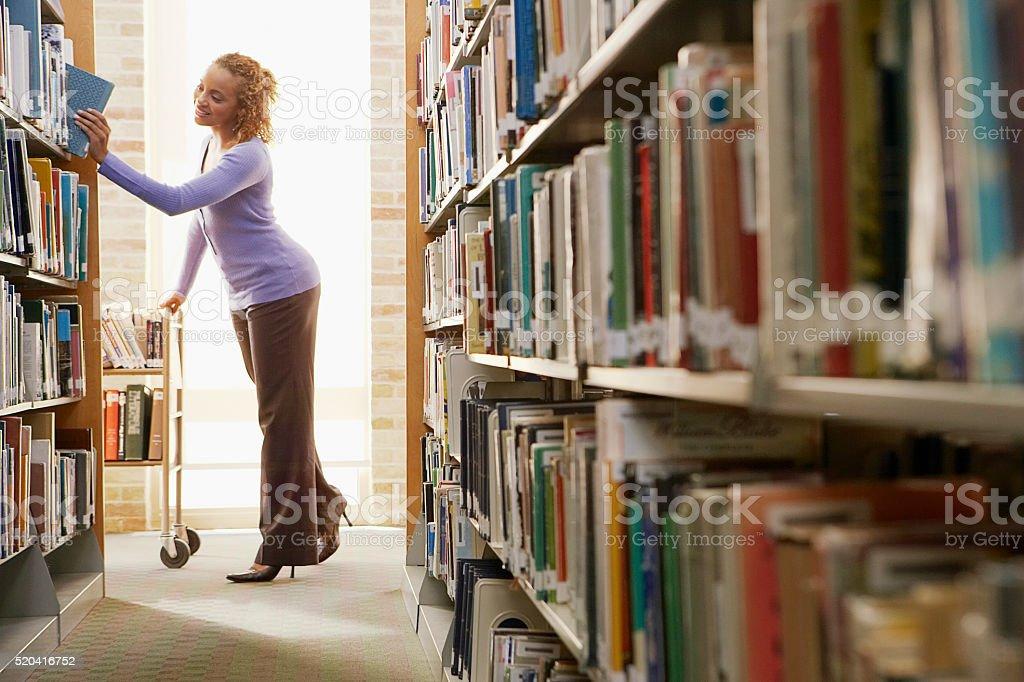 Librarian re-shelving books stock photo