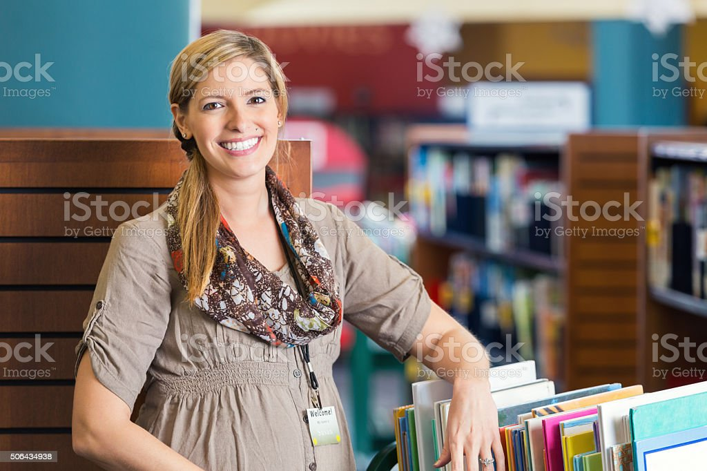 Librarian smiling near book cart in modern public library stock photo