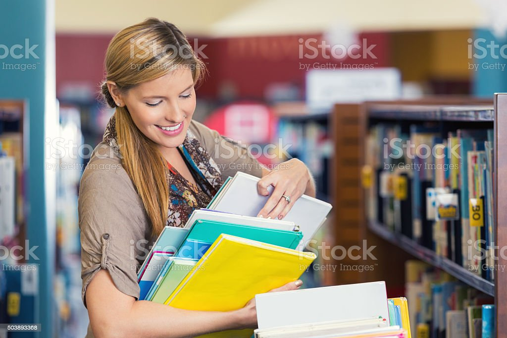 Librarian sorting childrens' books in public or elementary school library stock photo