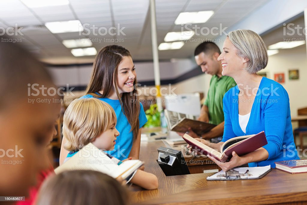 Librarian teacher helping students check out books in school library royalty-free stock photo