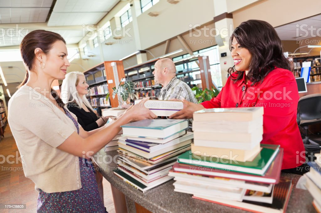 Librarians helping people check out books in the library stock photo