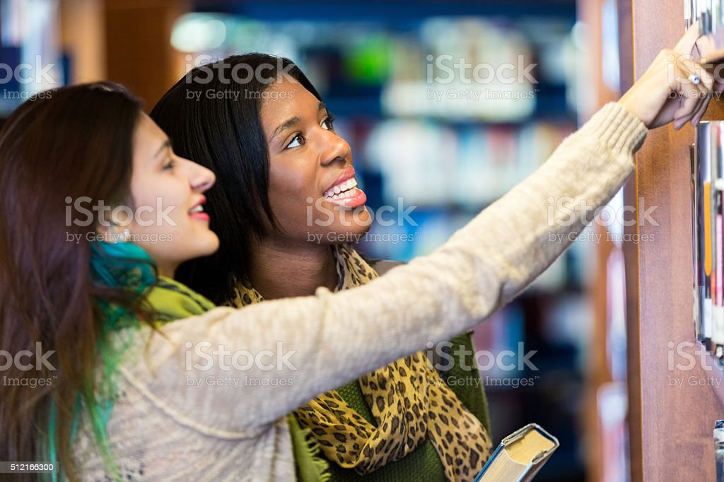 Library aid helping college student find book in library stock photo