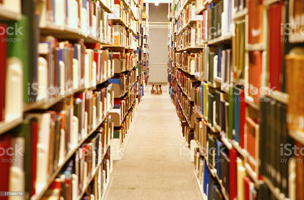 Library aisle lined with shelves and shelves of books royalty-free stock photo