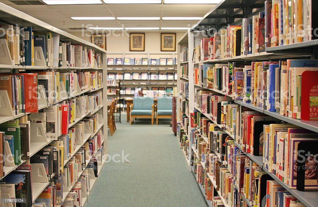 A library aisle of book shelves stock photo