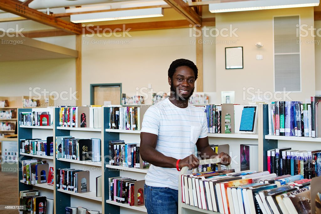 Library employee pushing book cart stock photo
