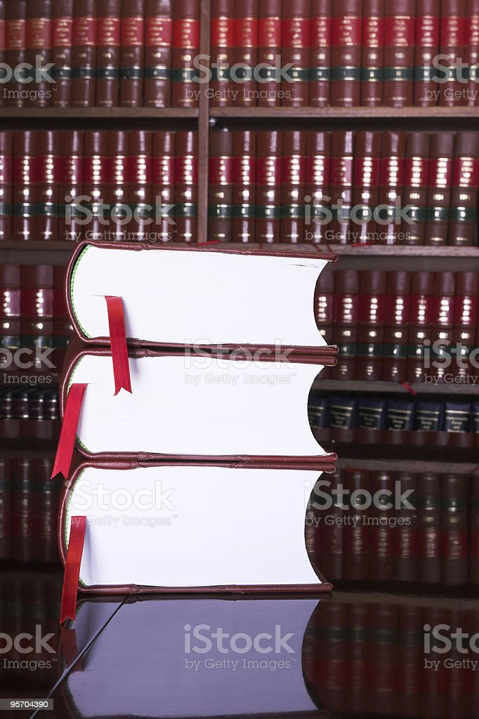 Library of legal books with three volumes in the foreground royalty-free stock photo