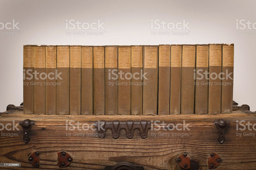 Library of Old Books Sitting on Vintage, Wood Trunk royalty-free stock photo