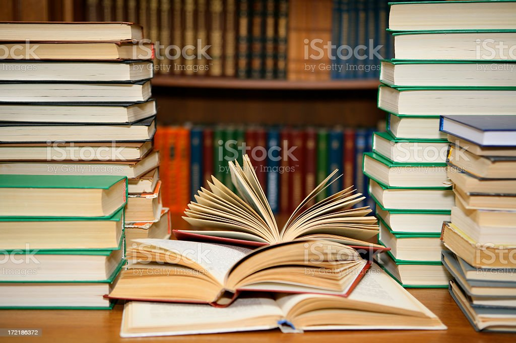 Library with stacks of books and two open books stock photo