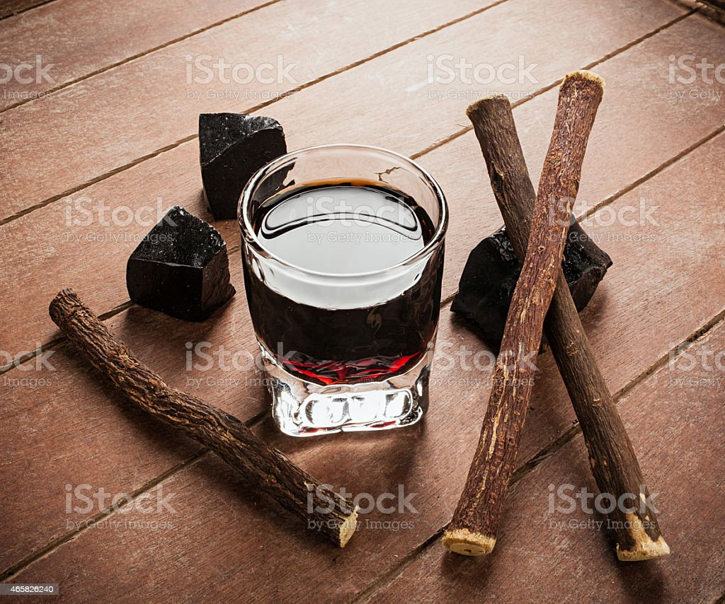 Licorice liqueur with pure blocks and roots. stock photo