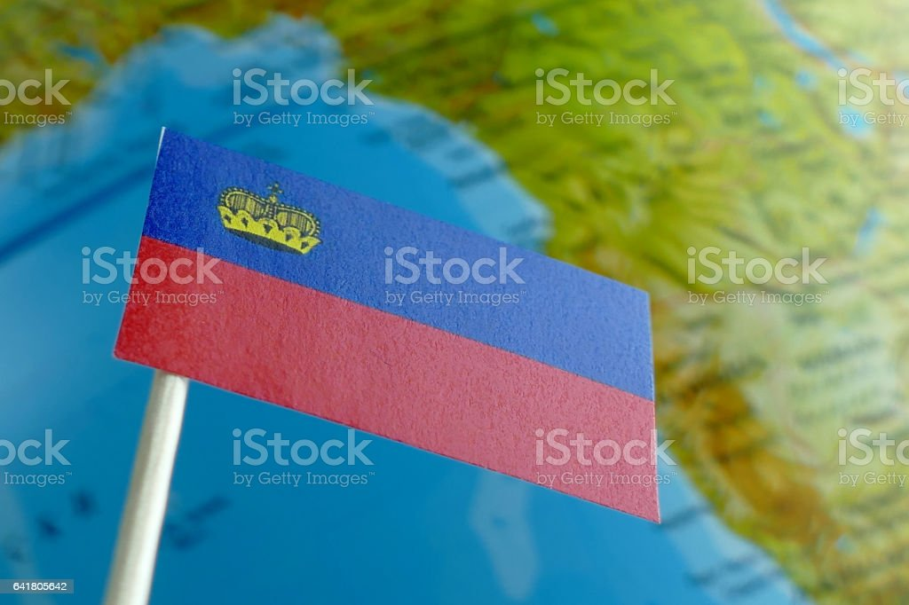 Liechtenstein flag with a globe map as a background macro stock photo