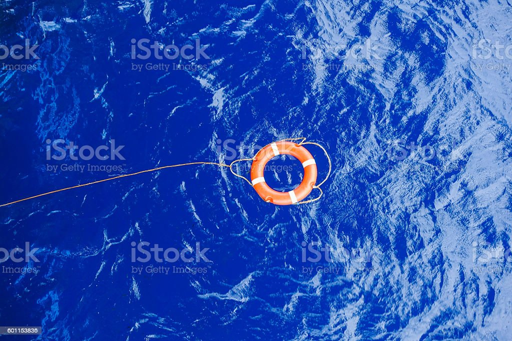 Life buoy bound with rope rescue floating in the sea. stock photo