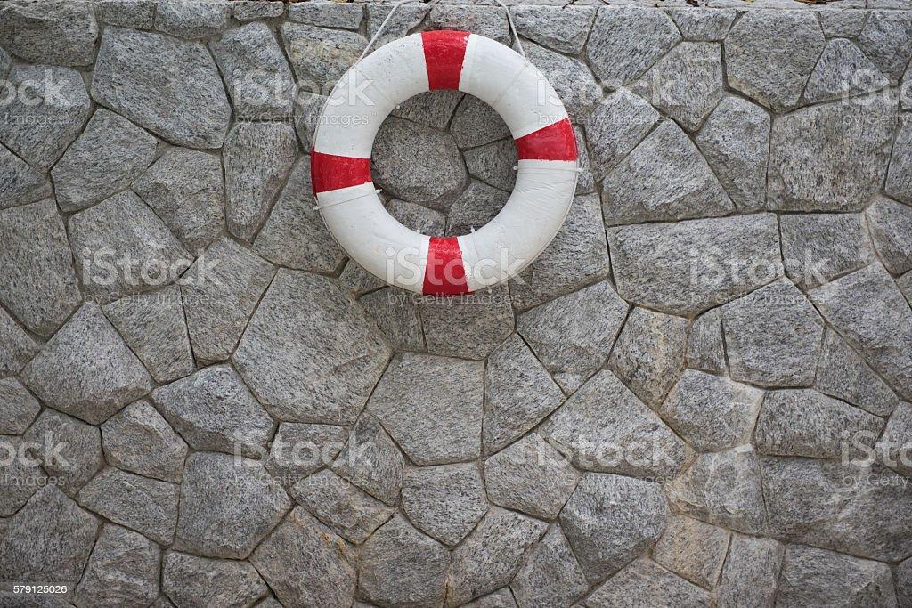 life buoy hanging on gray brick wall stock photo