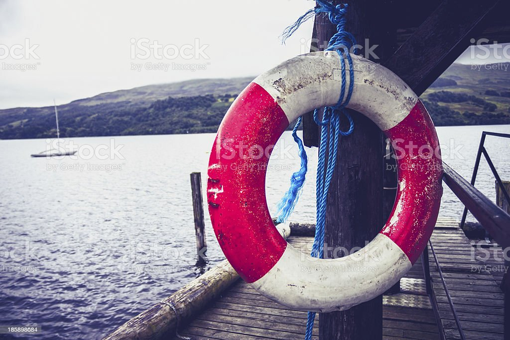 Life buoy hanging on pier at lake royalty-free stock photo