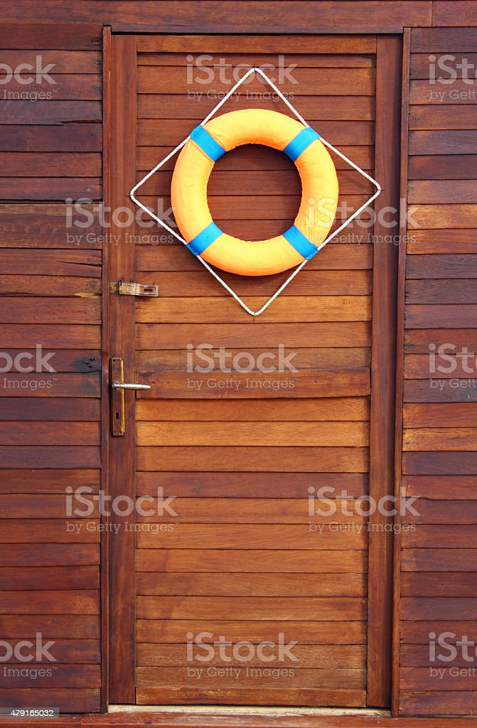 Life buoy hanging on wooden gate stock photo