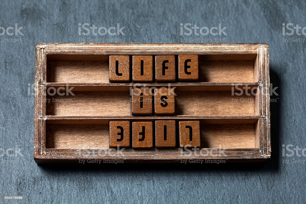 Life is life, opposite opponent concept. Shabby wooden box, cubes stock photo