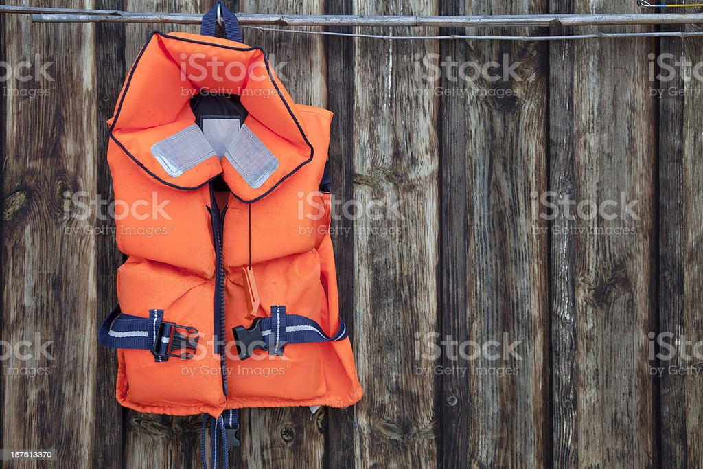 Life jacket for a child against an old wooden wall. stock photo