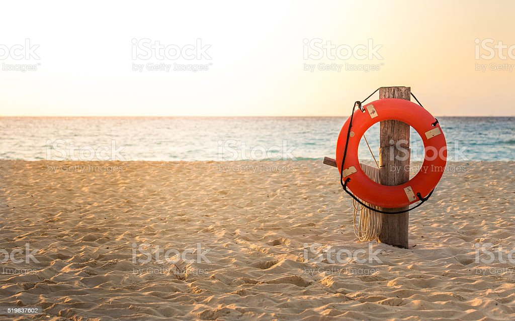 Life preserver on sandy beach stock photo