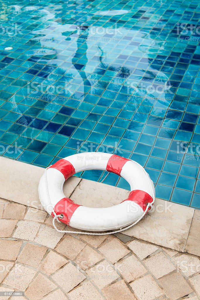 Life preserver white red lifebuoy with white ropes on tiled stock photo
