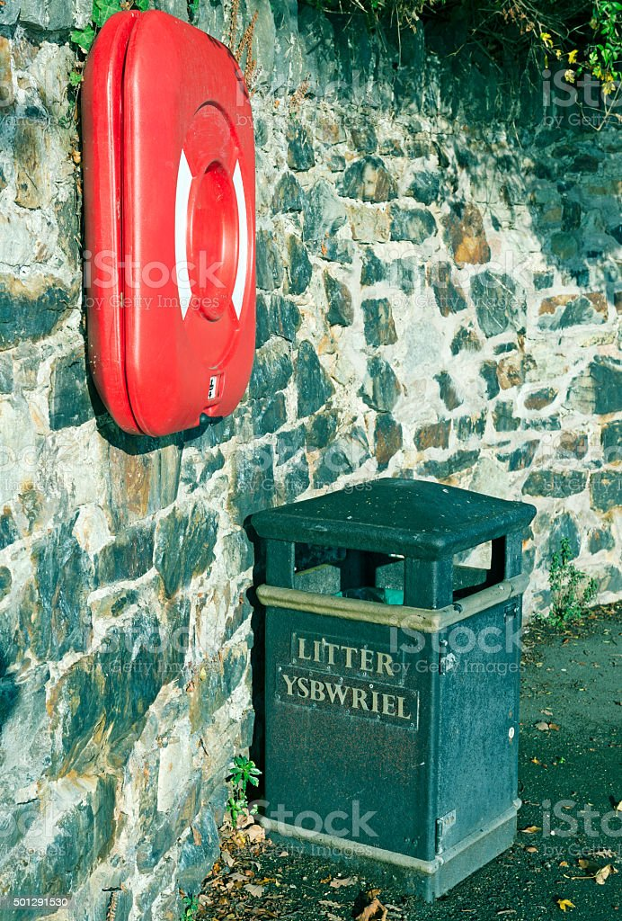 Life ring and litter barrel on shoreline walk in Wales stock photo