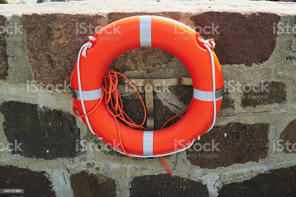 life ring with rope mounted at the wall stock photo